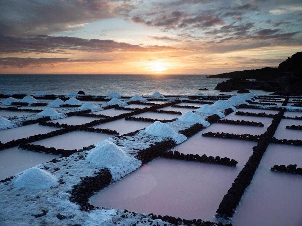 Pink sea water pools in a salination plant in front of an orange sunset
